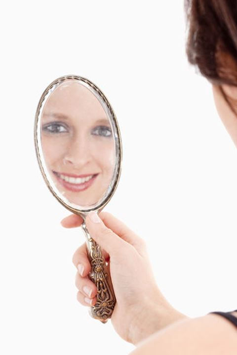 Young Woman Looking at her Reflection in Old Mirror - Isolated on White