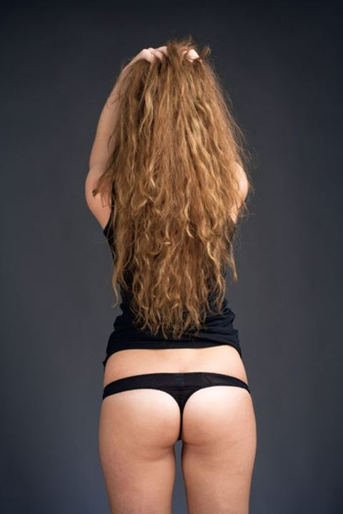 Rear View of a Young Woman with Long Brown Hair in Black Top and Panties
