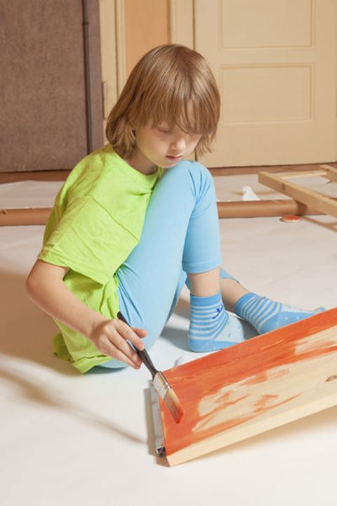 Boy with Blond Hair Painting a Board with Red Color