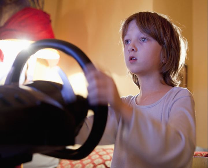 Boy Playing Racing Console Game with Steering Wheel