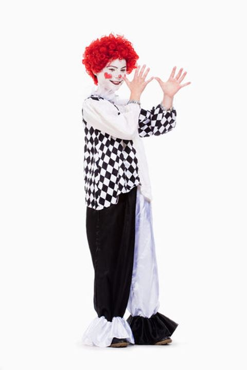Little Girl in Red Wig, Makeup and Outfit Posing as a Clown.