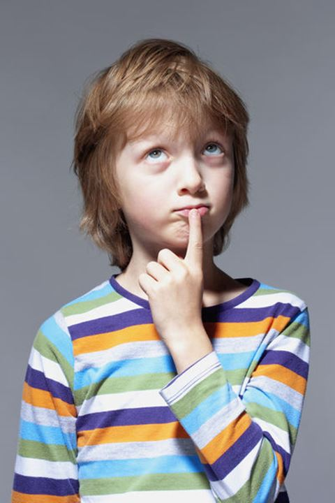 Boy Looking Thinking, Finger on his Mouth - Isolated on Gray
