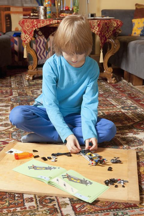 Boy Putting Together his Assembling Toys on the Floor