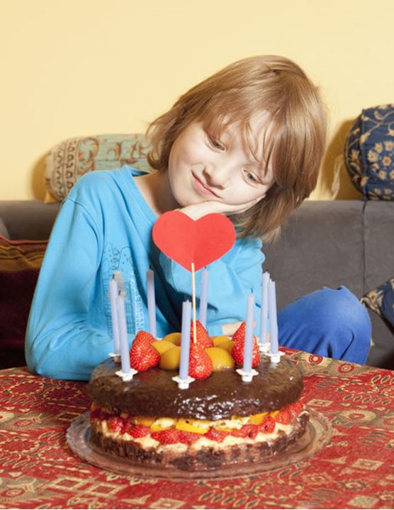 Boy with Blond Hair Looking at his Birthday Cake