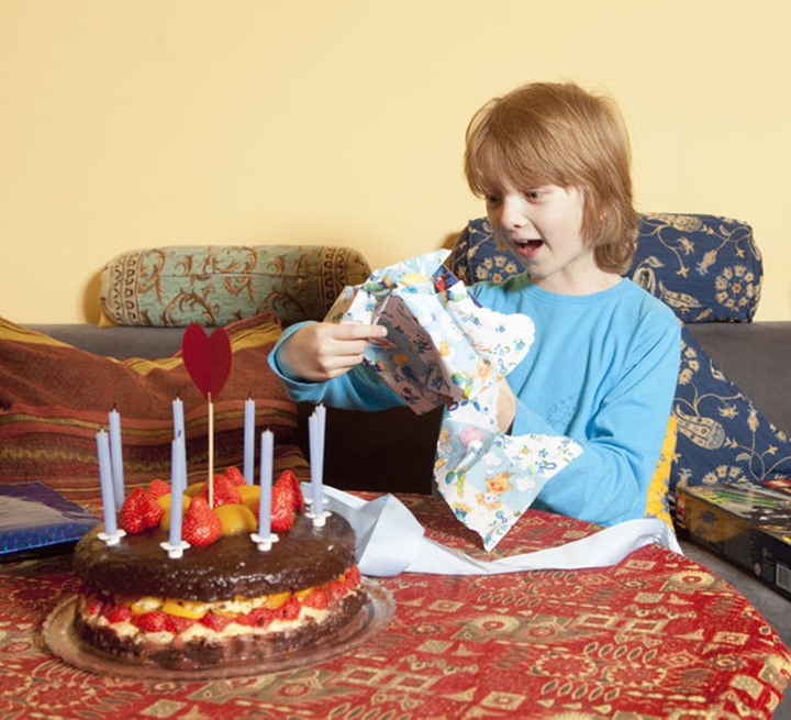 Boy with Blond Hair Opening his Birthday Presents