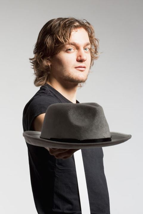 Young Man Stretching out his Arm with Hat