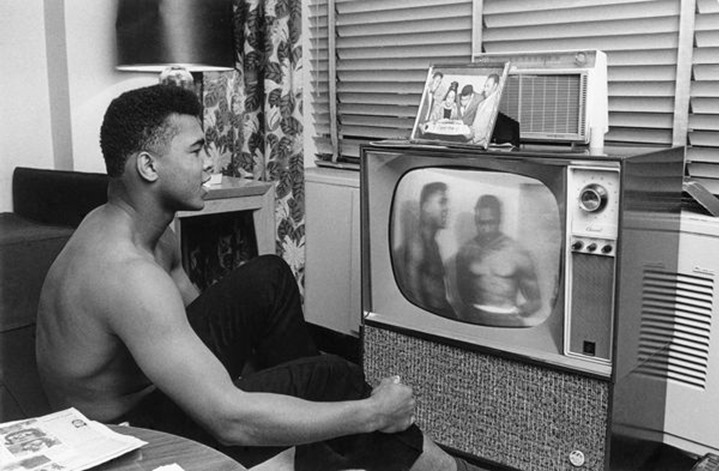 Cassius Clay watching himself and Sonny Liston on TV. Pittsburgh, Ohio, USA, 1963.