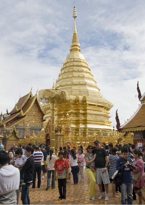 A group of people in front of the golden Chedi in the Wat Phra That Doi Suthep temple, Chiang Mai, Thailand