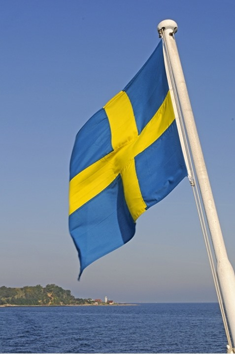 The swedish flag on a boat on Oresund strait, Ven island in background, Sweden.