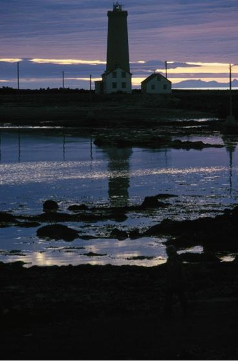 Lighthouse and a small building reflecting in a pool of water.