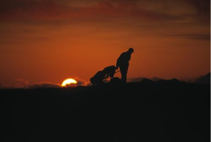 A man with a golfbag in midnight sun