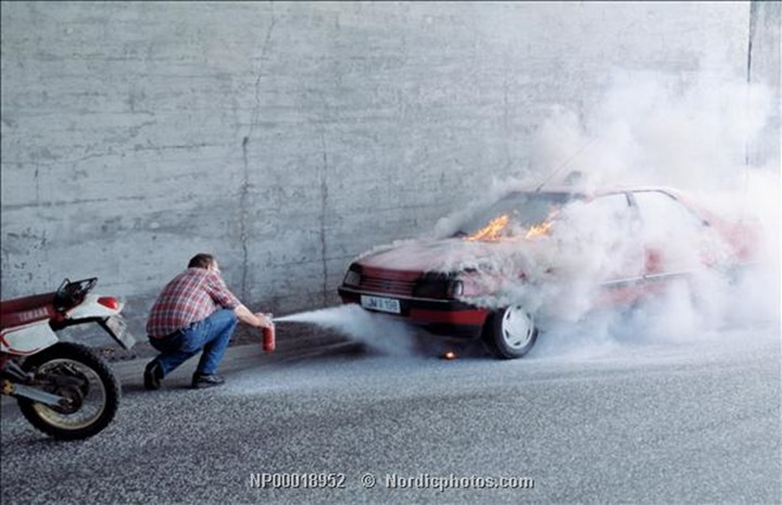 A man putting out fire in a car with a fire extinguisher.