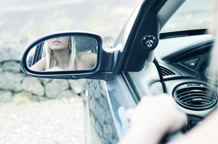 A young woman sitting in a driver's seat of a car, reflecting in the rear view mirror