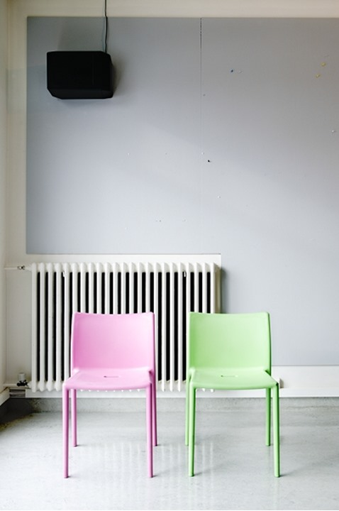 Two chairs side by side, one pink and the other green