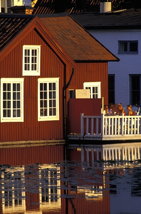 Sweden, Eskilstuna - people on porch by water
