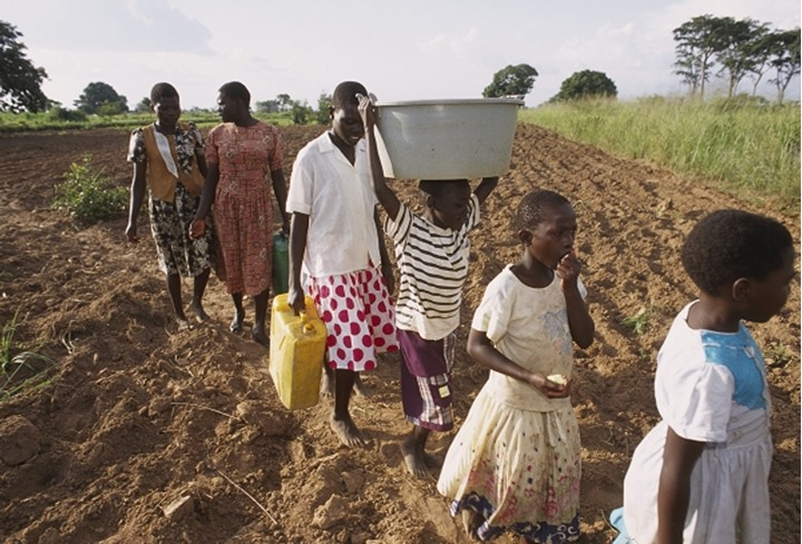 People moving in a queue to collect water in the containers at Uganda, Africa