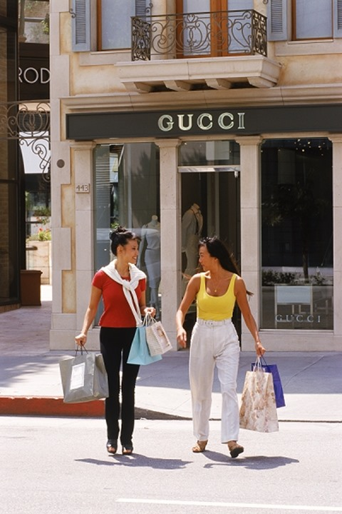 Two Asian women with shopping bags on lrodeo Drive in Beverly Hills, California.