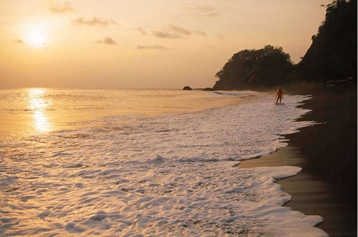Woman on black lava shores of Playa Hermosa on Pacific Coast of Costa Rica at sunset