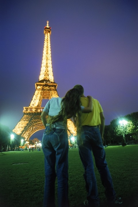 Rear view of couple embracing near Eiffel Tower at night