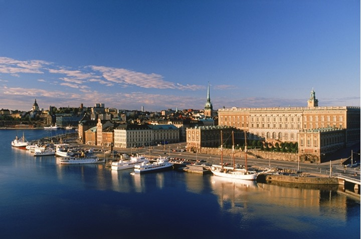 Boats anchored along Skeppsbron at sunrise with Royal Palace and Old Town in Stockholm