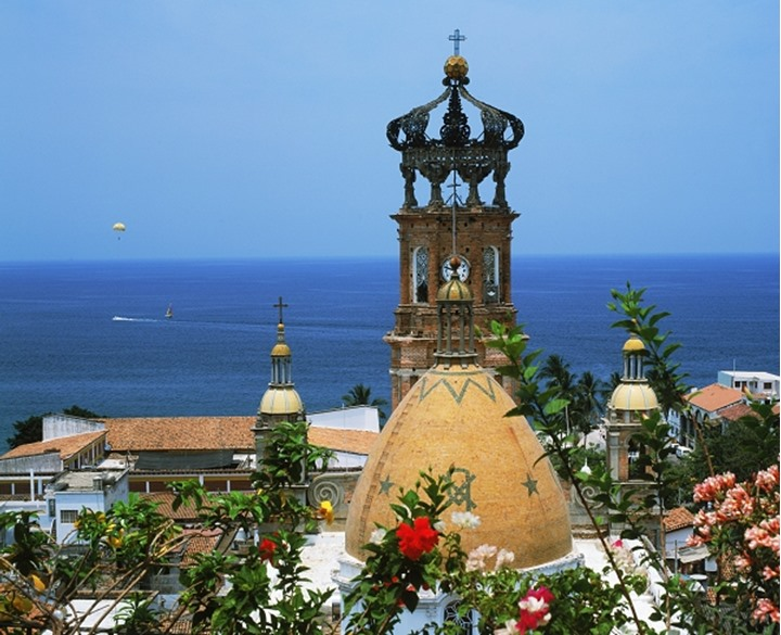 Guadalupe Church bell tower with flowers and parasailor over Pacific Ocean in Puerto Vallarta Mexico