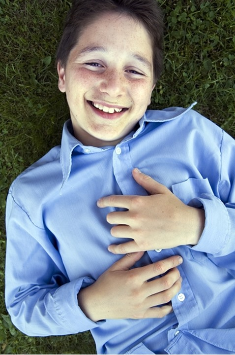 A teenage boy lying laughing on the ground