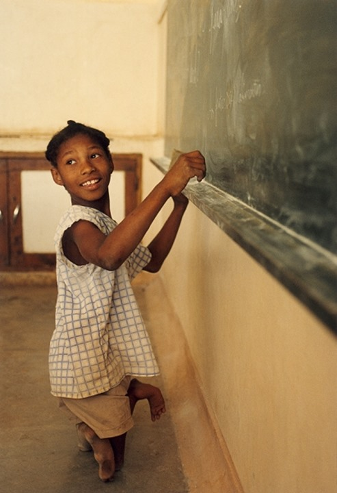 Side view of a handicapped child writing on the blackboard in Cape Verde