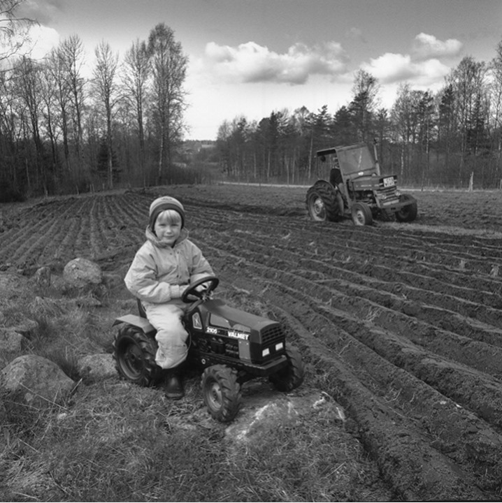 A boy on a toy tractor by a field which is being ploughed by a real tractor
