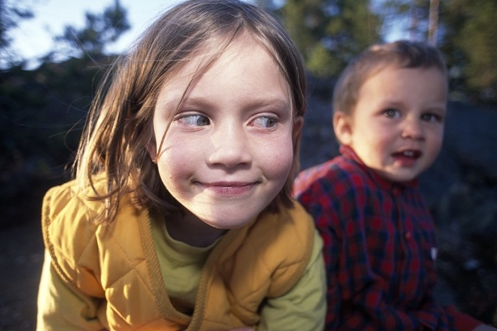 Close up view of a smiling girl looking at her brother