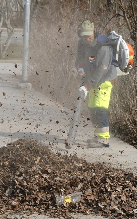 Man cleaning street whilst collecting autumn leaves with the help of a machine