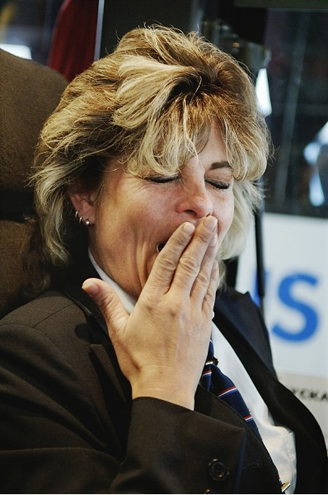 Close-up of a senior woman yawning with her hand over her mouth