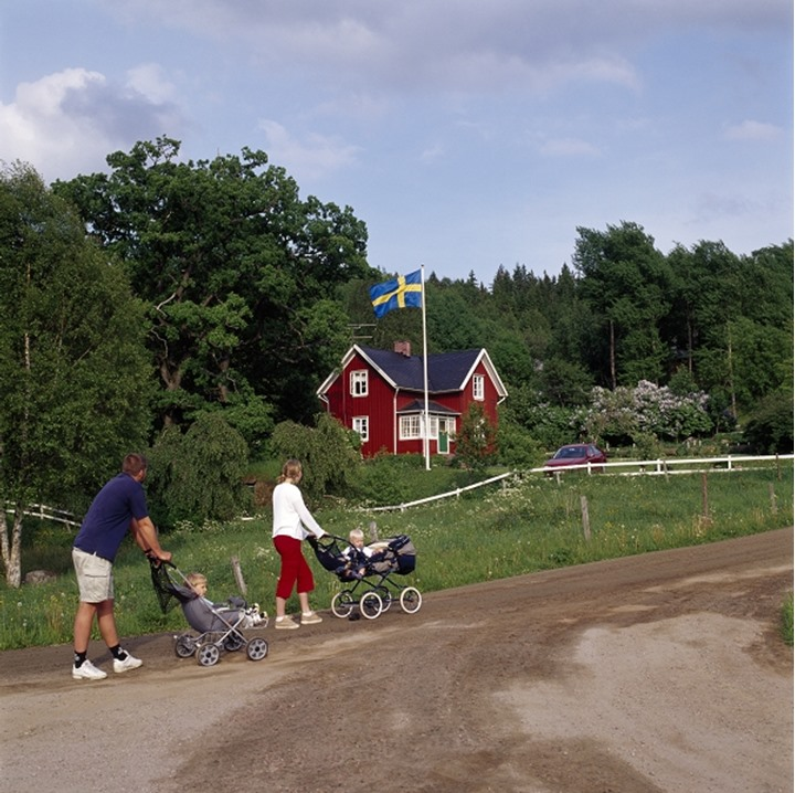 Side profile of a man and a woman pushing baby strollers,Molla,Västergötland,Sweden