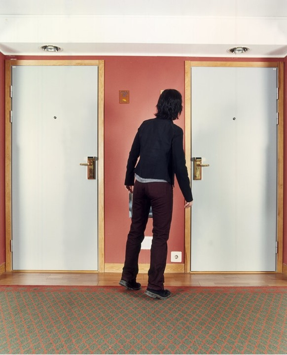 A young man in front of two doors not knowing which is the right one