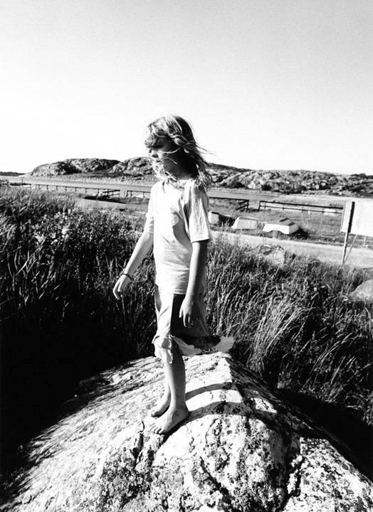 A girl standing on a windy stony hillock