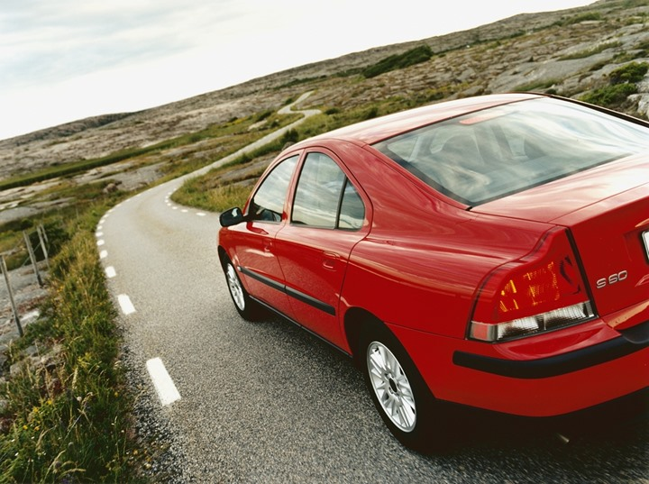 A red Volvo driving on a narrow country road